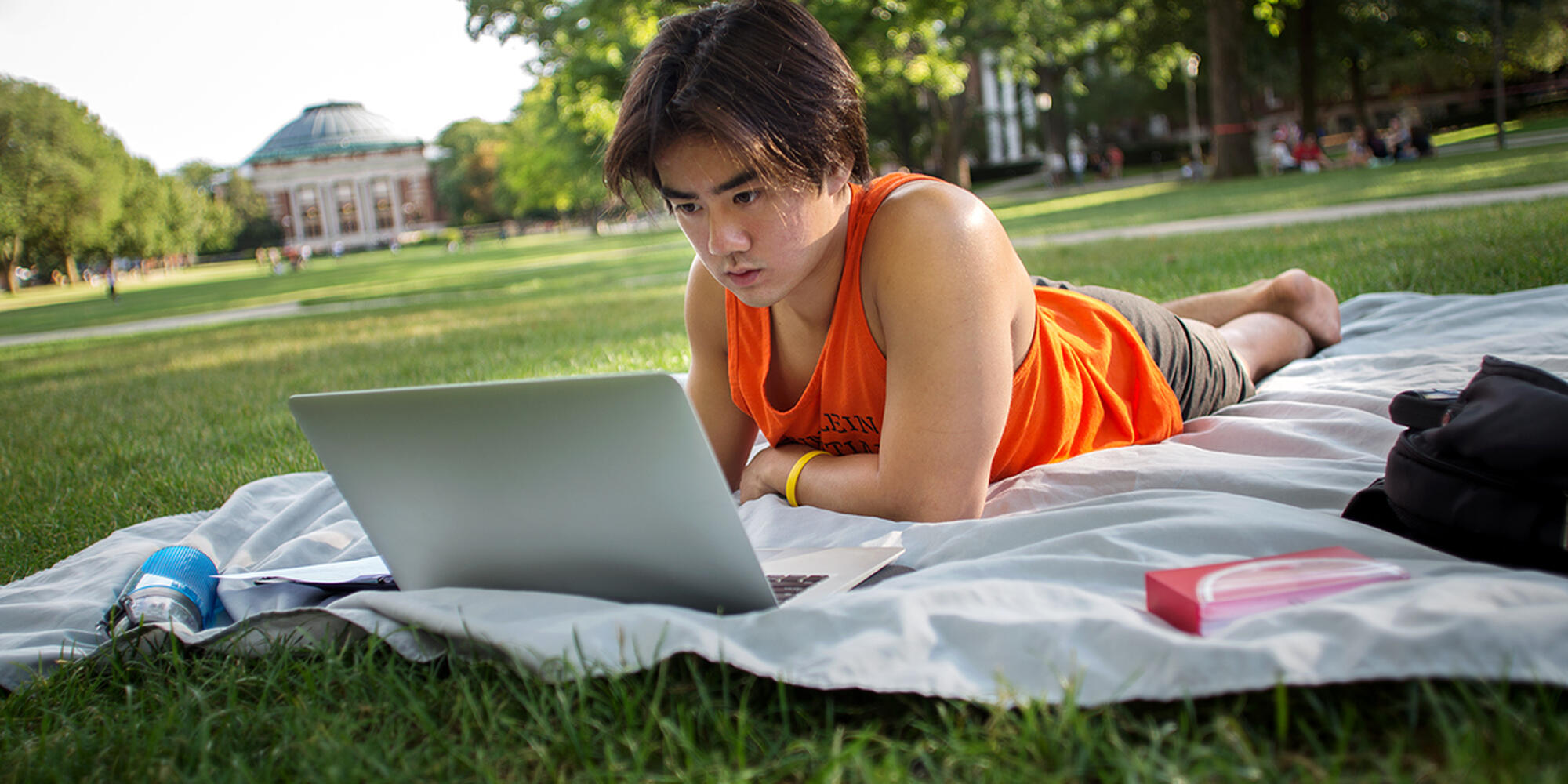 Student works on his computer on Main Quad.